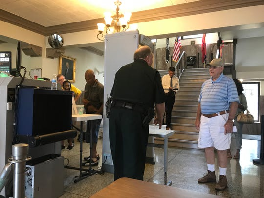 An officer tells a man visiting the Madison County Courthouse that all weapons, even those with carry permits, must be left in the car before entering the building.