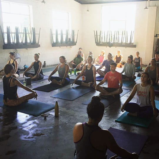 The class sits in a basic yoga pose at Printshop Beer Co. on Sevier Avenue. August 2018.