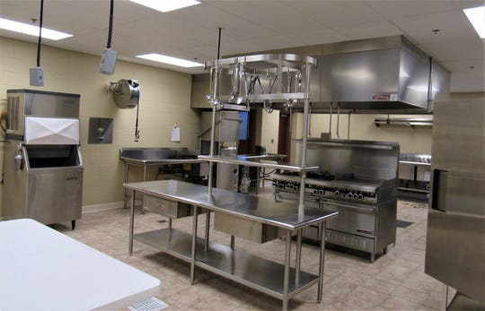 The community center's commercial kitchen is set up for catering to large groups; it is designed for efficiency and easy cleaning.  A smaller warming kitchen for pre-prepared food is nearby.