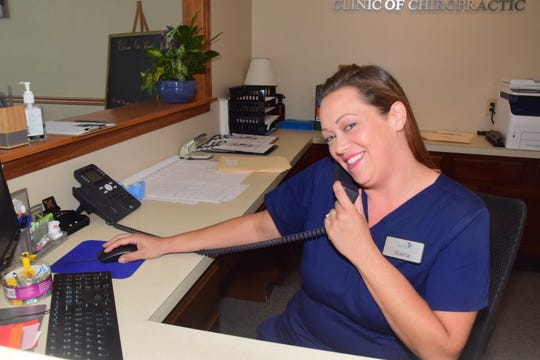 Office manager Alaina Vandermark, who graduated from Karns High in 1998, mans the front desk at Southeast Precision Clinic of Chiropractic Tuesday, Sept. 4, 2018.