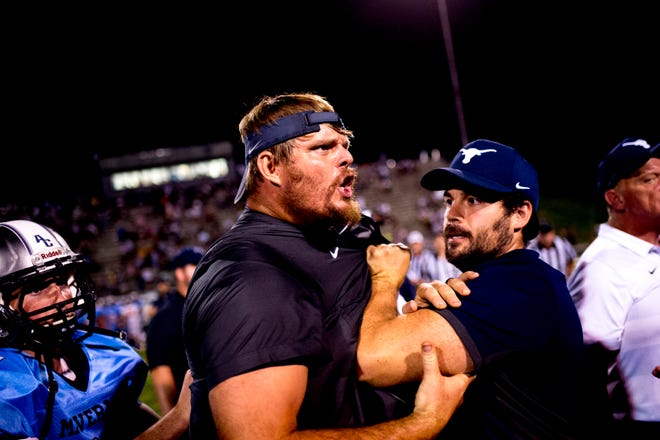 Anderson County offensive line coach Russ Gillum is held back after getting into an apparent altercation with Clinton coach Randy McKamey  during a football game between Anderson County and Clinton at Anderson County High School in Clinton, Tennessee on Thursday, September 6, 2018.