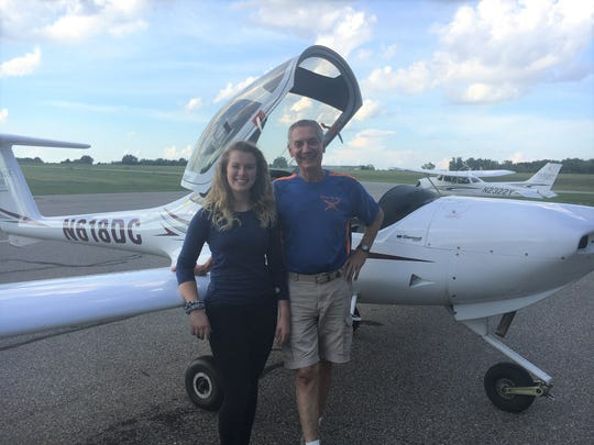 Aspiring fighter pilot Lauren Dowd and her Crosswinds Aviation flight instructor Ron Megesi celebrate her 17th birthday and first solo flight, Tuesday, Sept. 4, 2018, at the Livingston County Spencer J. Hardy Airport in Howell Township.