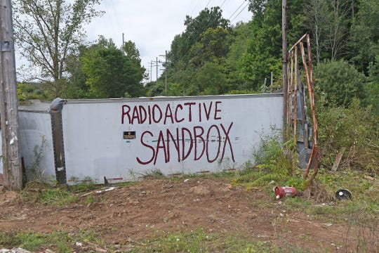 """A message reading """"radioactive sandbox"""" is painted on a wall of Al Hogan's former property at 663 Fifth Ave. Friday. The property was sold at a sheriff's sale earlier in the day."""