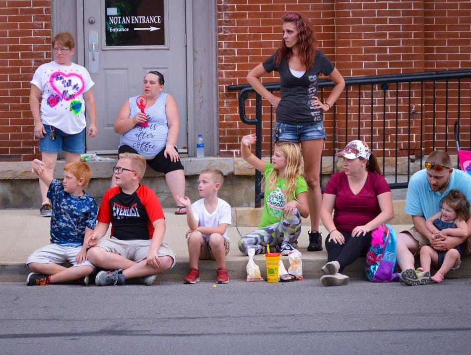 Children watch and wave as the Marion Popcorn Festival parade passes on Thursday, Sept. 6, 2018.