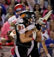 Hartford's Scott Savage is pulled down by Slinger's Deven Hayes.