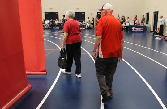 Ronald and Marilyn Woolsey work their way through partitions to watch a Brookfield East junior varsity boys volleyball game from their favorite position high in the bleachers and mid court on Sept 6.