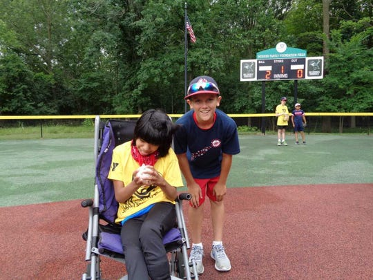 Volunteers are paired with kids to help them play baseball through the YMCA Miracle League of Milwaukee.