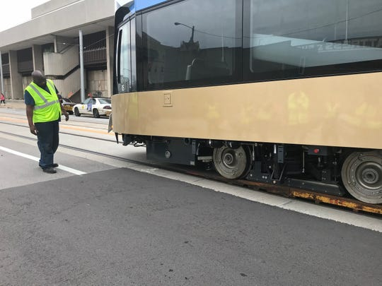 City of Milwaukee employee Stephan Barber helps guide the last of five streetcars onto the rails in downtown Milwaukee. Daytime testing of the streetcar service, known as The Hop, begins later this month