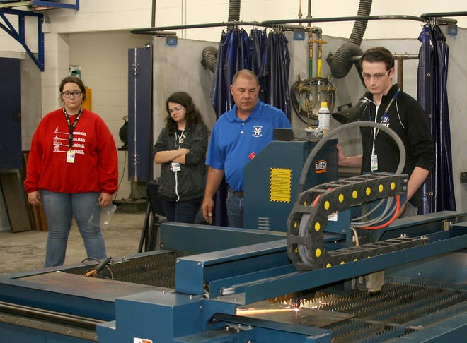 Junior Arno Justman (far right) demonstrates how the ACME Academy's plasma cutter operates. Members of the board of education and district administrators got a tutorial on how the machine works from juniors (from left) Peyton Barton and Hailey Bark, and agriculture instructor Owen Carpenter.