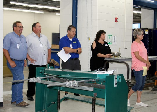 Mountain Home Public School Board Secretary Arnold Knox (from left), high school principal Brent Bogy, and board members Dan Smakal, Lisa House and Barbara Horton attended a demonstration Thursday afternoon from agriculture instructor Owen Carpenter and his students about the ACME Academy's plasma cutter.