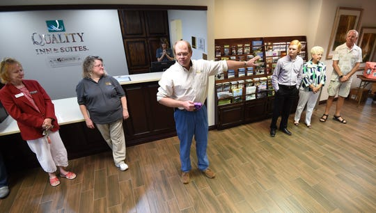 Quality Inn and Suites owner/general manager Ricky Johnson (center) addresses guests Thursday at an open house to celebrate the hotel's renovations.
