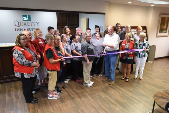 Members of the Mountain Home Area Chamber of Commerce and the staff of Quality Inn and Suites Mountain Home huddle together for a ribbon-cutting ceremony Thursday in the hotel's lobby.