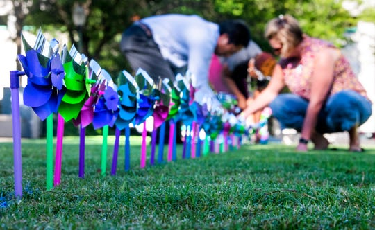 Gift of Life staff and volunteers, including students from Valiant Cross Academy, place pinwheels, representing infants deaths in Alabama last year in RSA Park in front of the RSA Tower in Montgomery, Ala., on Friday September 7, 2018. There are 537 for infant deaths and 569 for fetal deaths.