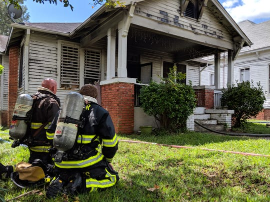 Two Montgomery firefighters rest as Montgomery Fire/Rescue works to put out a house fire at the 400 block of Burton Avenue in Montgomery, Ala., on Sept. 7, 2018.