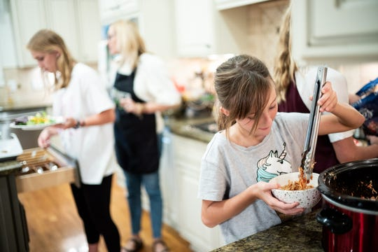Ruby Ward, 9, serves herself dinner while eating with her family at their home in Franklin on Sept. 6, 2018. The family recently completed a two-month technology blackout with hopes of reconnecting as a family.