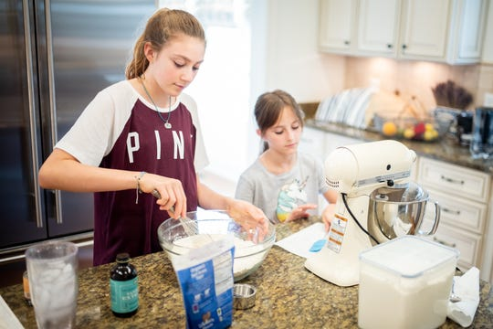 Ava Claire Ward, 13, and Ruby Ward, 9, bake cookies at their home in Franklin on Sept. 6, 2018. The family recently completed a two-month technology blackout with hopes of reconnecting as a family.
