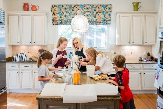 From left, Ruby Ward, 9, Ava Claire Ward, 13, Shannon Ward, Grace McNamee-Green, 17, and Bennett Ward, 9, bake cookies Sept. 6, 2018.