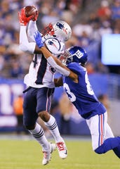 New England Patriots defensive back J.C. Jackson (34) intercepts a pass intended for New York Giants wide receiver Kalif Raymond (83) during the first half at MetLife Stadium on Aug. 30, 2018 in East Rutherford, N.J.