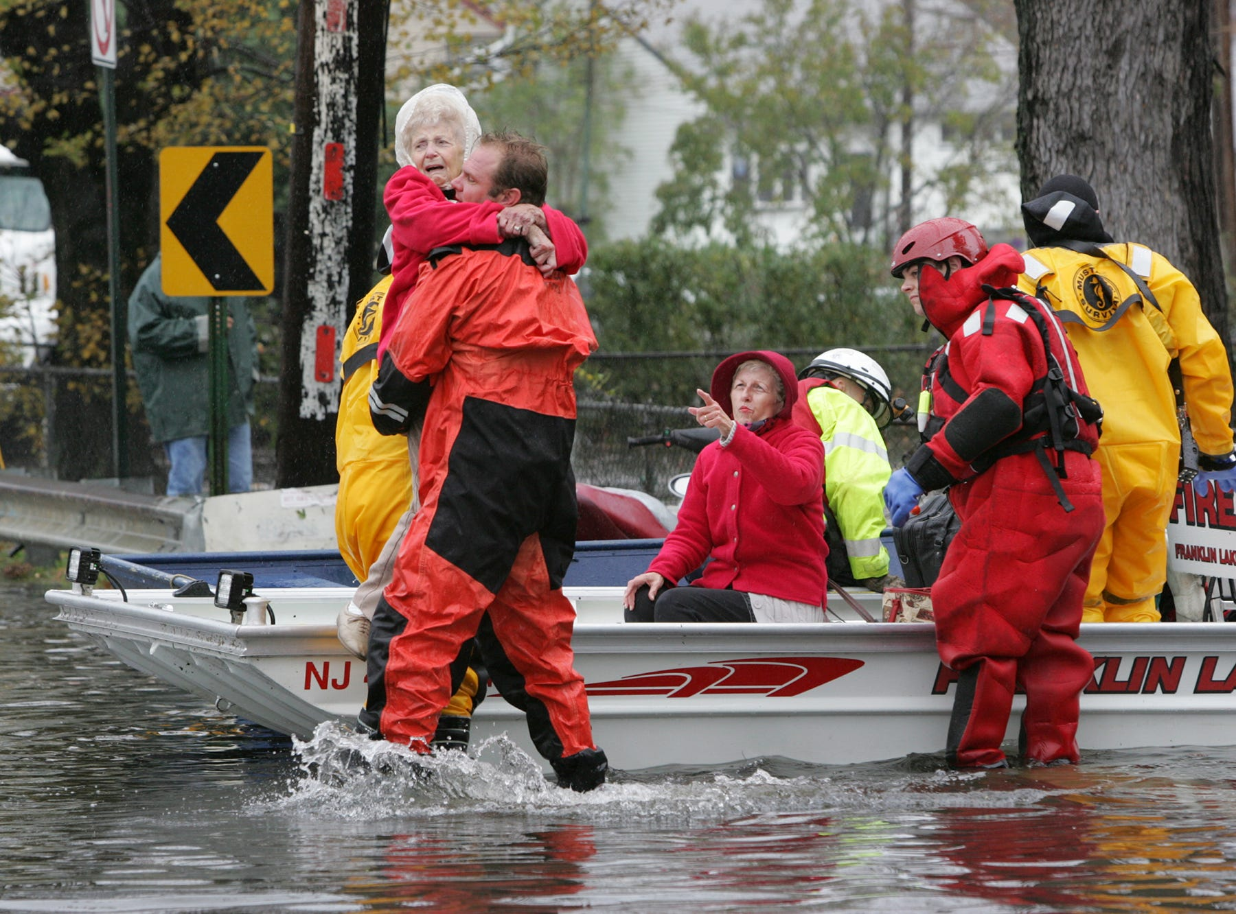A rescue worker carries an elderly woman to dry ground after rescuing her from her Little Ferry home on Oct. 30, 2012.