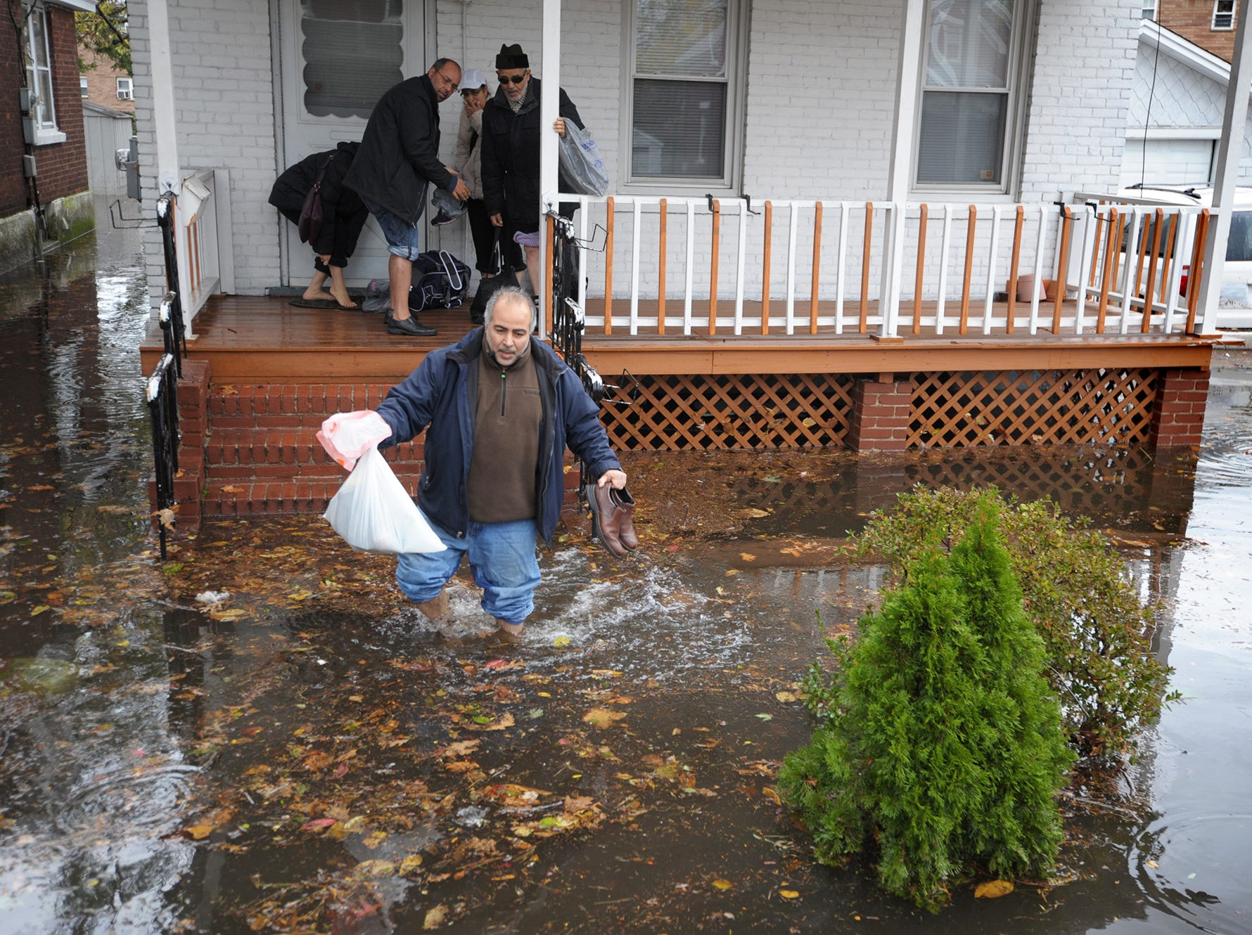 Little Ferry --- Tuesday October 30, 2012  --- Matid Amini wades through water in front of his Columbus Ave. home in Little Ferry to good samaritan Garfield resident John Mercadante personal truck, where Amini was then transported to a shelter at BC Vocational Technology School in Teteboro. Amini was evacuated with 4 of his family members after they were stranded after Hurricane Sandy.