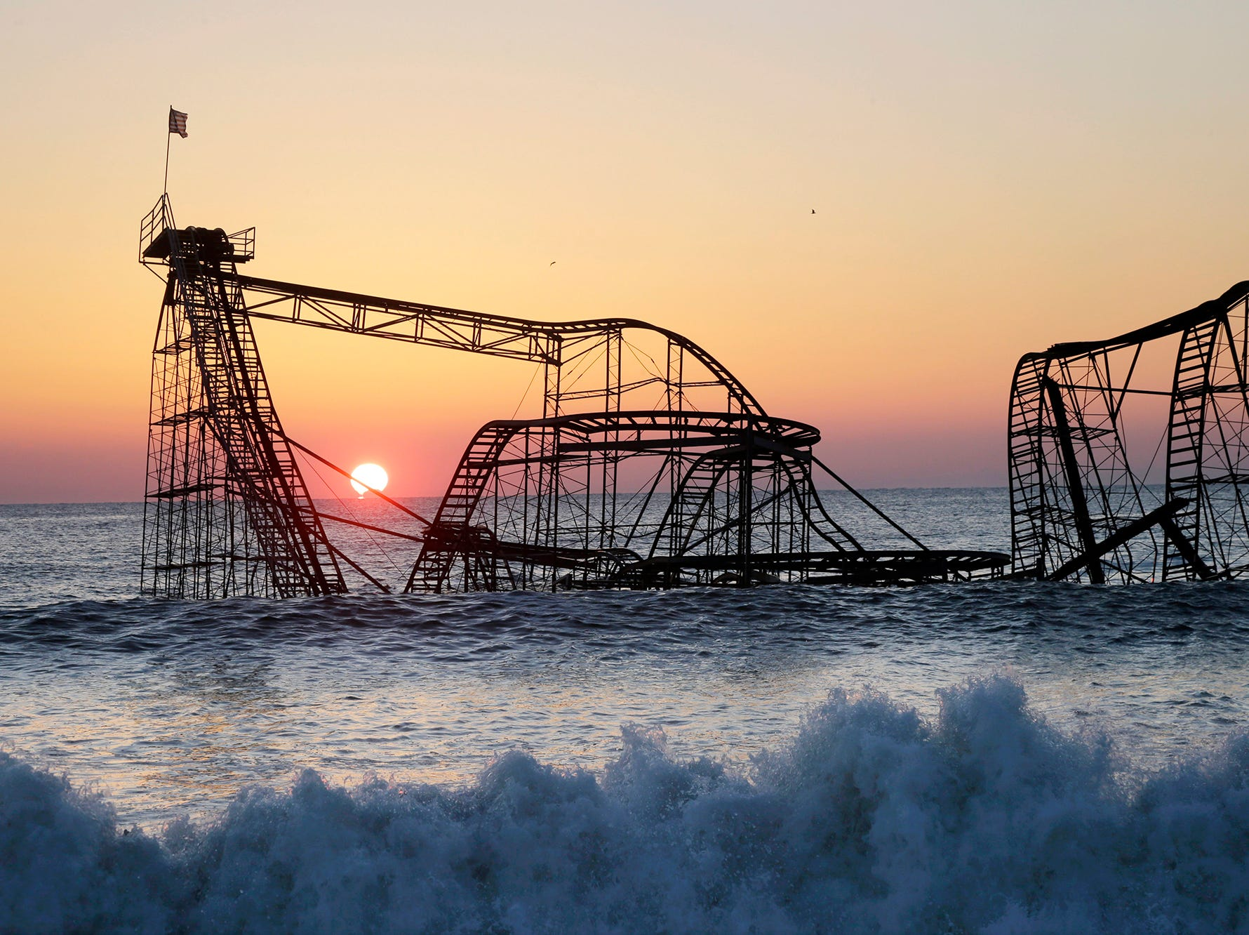 In a Feb. 25, 2013 file photo, the sun rises in Seaside Heights, N.J., behind the Jet Star Roller Coaster which has been sitting in the ocean after part of the Funtown Pier was destroyed during Superstorm Sandy. Work is expected to start Tuesday afternoon, May 14, 2013 to remove the Jet Star coaster from the surf in Seaside Heights.