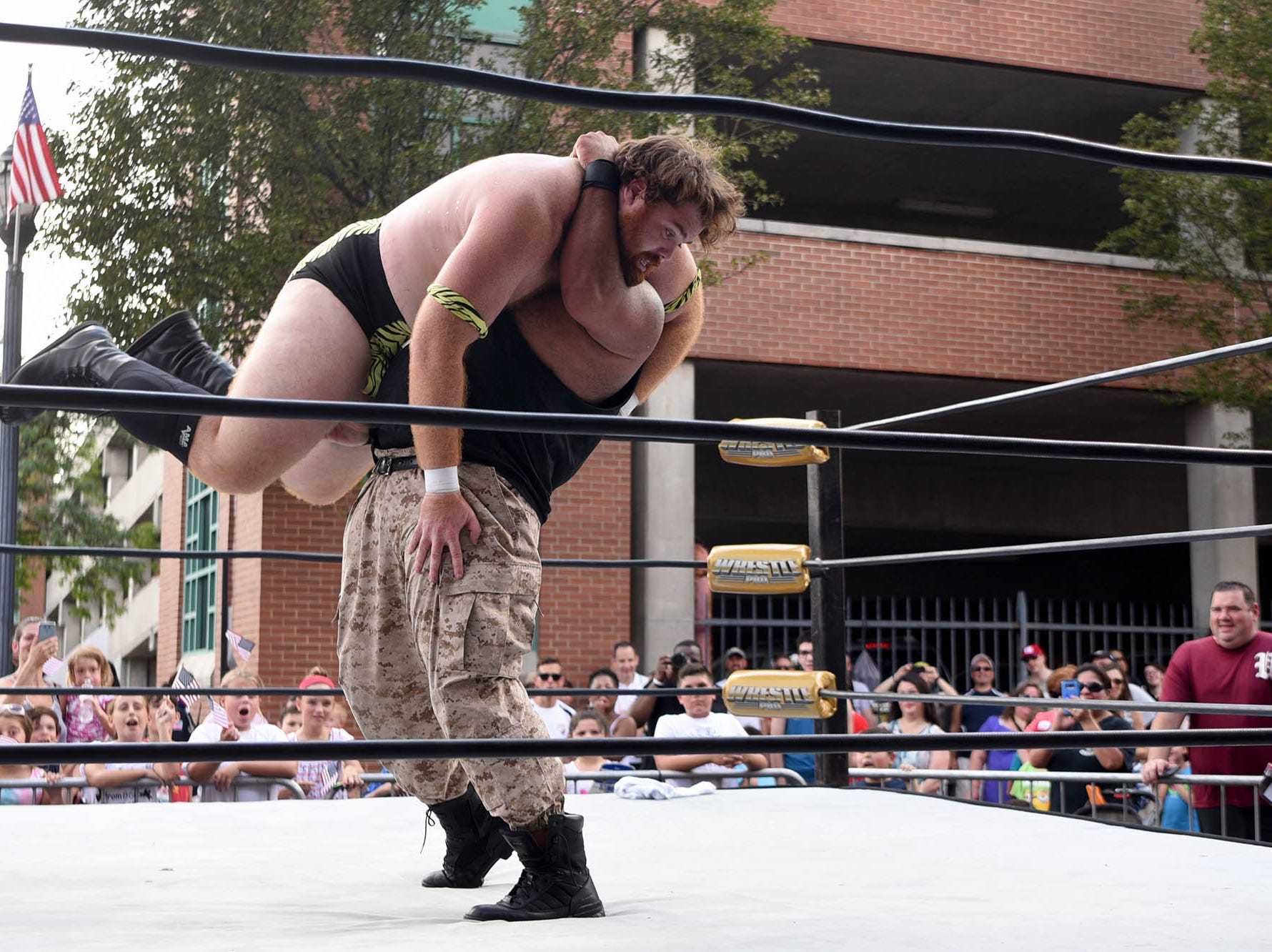 The 43rd annual Rutherford Labor Day Street Fair took place along Park Ave. in downtown Rutherford on Monday, September 3, 2018. Beefcake Charlie is lifted of the ground in a hold by Adam Payne during their match on Ames Ave. Payne won the match.
