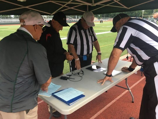 Referees prepare the replay tent at the Bergenfield-Ramapo game.