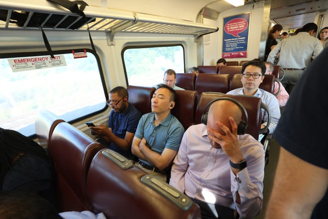 Most of the seats are taken while commuters try to get comfortable as the train fills up later in it's trip to Hoboken.