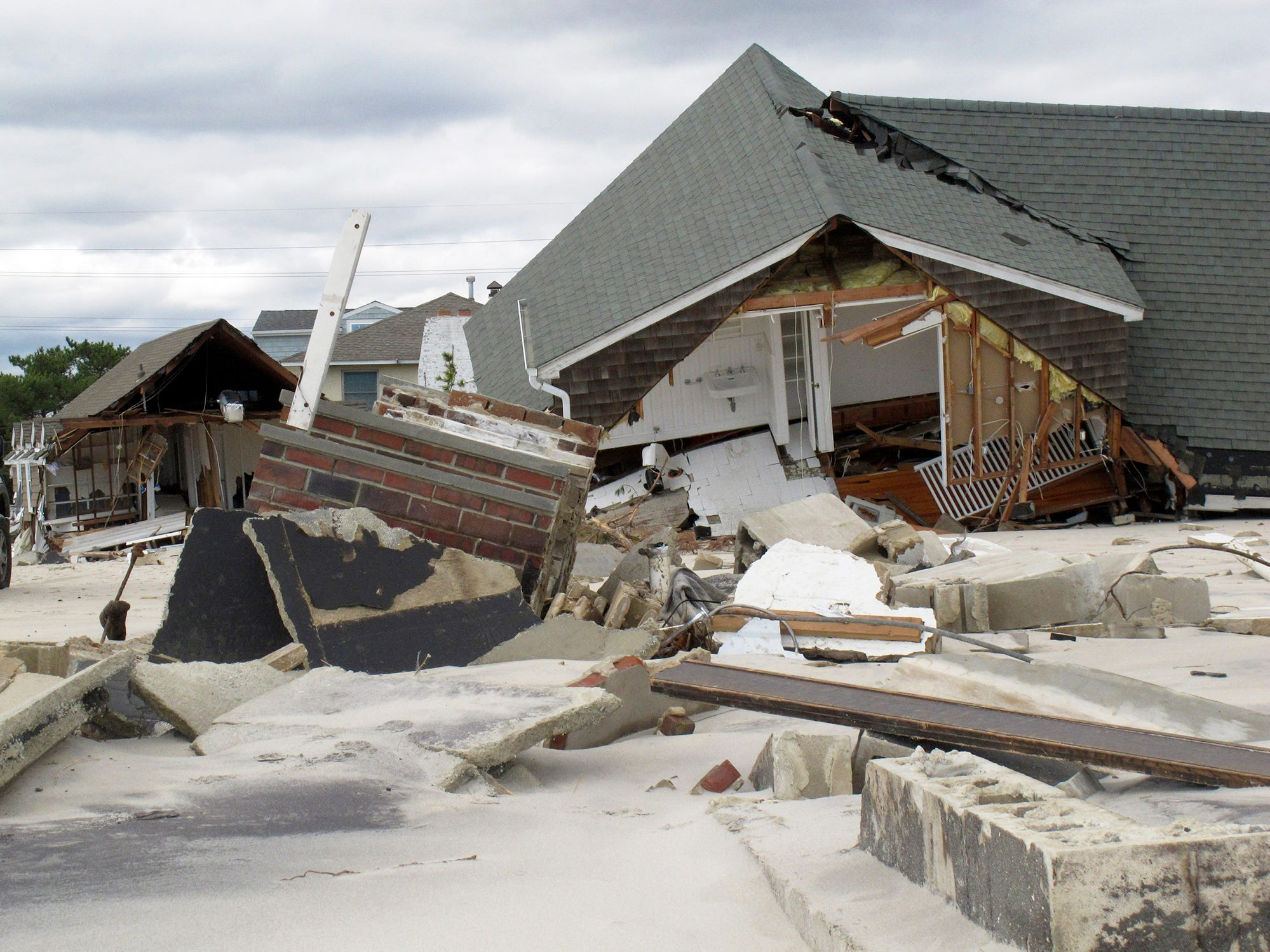 This Wednesday, Oct. 31 2012 photo shows one of many destroyed oceanfront homes in Mantoloking, N.J.  2012 in the aftermath of Hurricane Sandy. Most of the multimillion-dollar homes along this old-money stretch of the Jersey shore were seriously damaged by pounding surf, wild wind and, in some cases, fire from ruptured gas lines. Numerous homes were destroyed, and some were obliterated, leaving behind just empty sand or maybe a few broken pilings jutting up out of the surf.