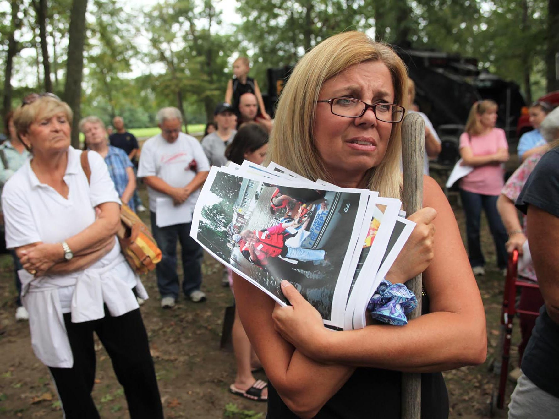 Christy Collichio, of Paramus, holds photographs of a flooded Rochelle Parkway in Saddle Brook, where her mother was evacuated from during hurricane Irene. About 200 local residents came out to demand that a solution be found to prevent the flooding of homes near the Saddle Brook River Sunday afternoon at Saddle River Park.