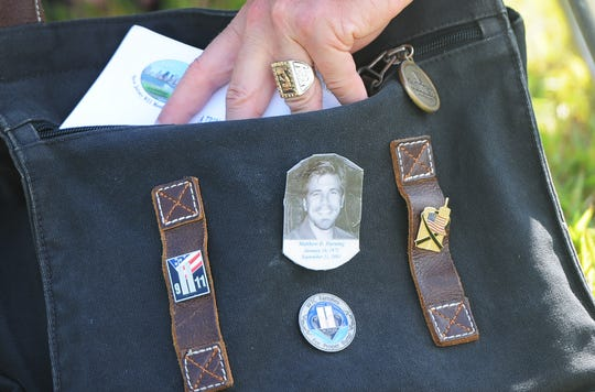 A photo of Matthew Horning, a victim of 9/11, is seen on the briefcase of his father, Kurt, during the Empty Sky Memorial Ceremony at Liberty State Park on September 7, 2014.