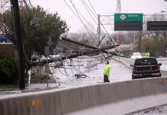 A PSE&G worker inspects downed power lines and poles on Paterson Plank Road behind the sports complex in the Meadowlands after Superstorm Sandy in 2012. The PSE&G official said there were 14 poles damaged.