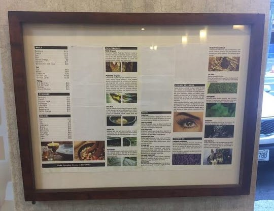 A framed brochure, hanging on the wall at the nail salon, now has blank spaces where it once advertised services in massage therapy.