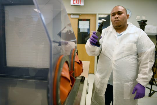 Jonathan Holly, a forensic scientist with the New York City Office of Chief Medical Examiner, explains the first step of cleaning, examining and removing debris from bones in process used to help identify remains of deceased victims. The unit handles DNA testing for unidentified persons, including victims of the attacks on the World Trade Center on 9/11.