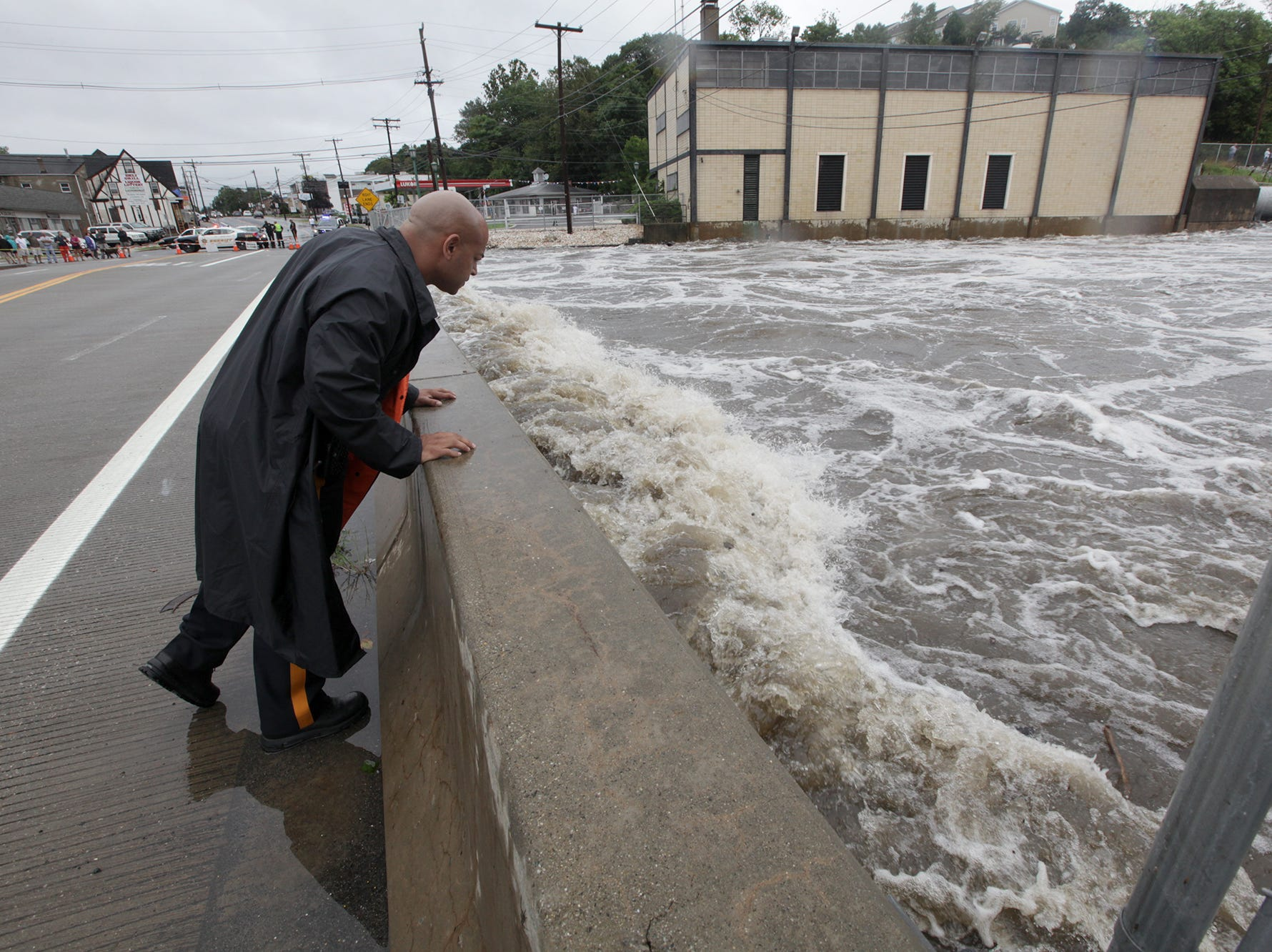 Passaic County Sheriff's Officer Ray Galan looks at the rushing flood waters that passed through the dam crash into the bridge that is part of Hamburg Turnpike.