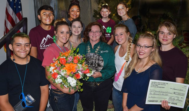 Molly Hayes, middle, is surrounded by 4-H members she has worked with over the years. Hayes is the National 4-H Salute to Excellence 4-H Volunteer of the Year. Celebrating her award are, front from left, Joel Gonzales, Lauren Wilder, Kaityn Davis, Ashtyn Leden, Emily Heine and Bethany Heine. Back from left are Evan Garcia, Casey Hendren, RaeAnna Gallegos and Brooklyn Powel.