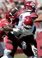 In this Sept. 30, 2017, file photo, New Mexico State kick returner Jason Huntley fumbles the ball as he is hit by Arkansas defender Micahh Smith on a kickoff return in the second half of an NCAA college football game in Fayetteville, Ark.