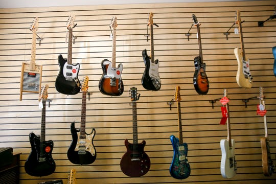 Guitars are displayed on a wall, Thursday, Sept. 6, 2018 Main Street Music at 210 South Main Avenue in Aztec.