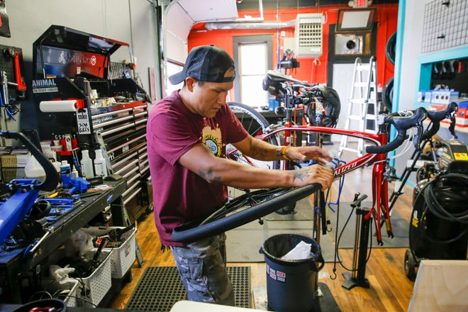 Anthony Kady, lead mechanic at Alien Bike Shop works on a customer's bike,  Thursday, Sept. 7, 2018 at the bike shop on South Main Avenue in Aztec.