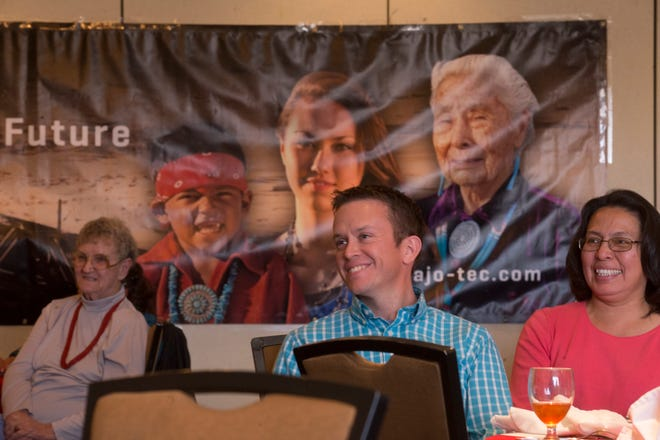 Randall Jeffrey, center, the development director for Navajo Ministries, smiles after receiving an NTEC Community Benefit Fund award on Dec. 14, 2017, at the Courtyard by Marriott Farmington.