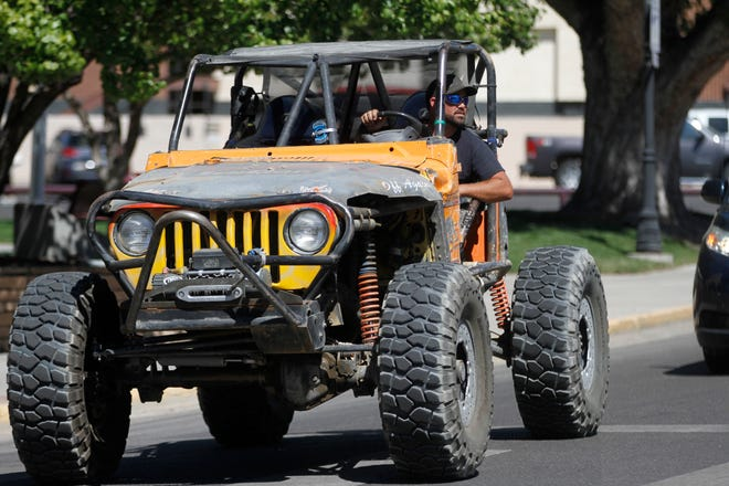 """Rick Jenkins drives his 2000 Jeep Wrangler,  named """"Cheeto,"""" through the intersection of North Orchard Avenue and West Main Main Street, Friday to join friends during a lunch event for the Four Corners 4x4 Week in Farmington."""