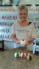 Glazy Days owner Jill French shows off  jack-o-lantern votive candle holders. Customers can paint pumpkins like these for $5 during South Lyon's annual Pumpkinfest, which runs Sept. 28-30.