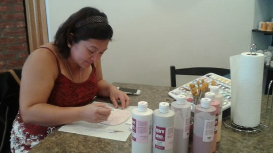 Audrey Lim of South Lyon works on an intricate design at the Glazy Days studio.