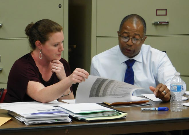 Tressa Miller, finance director, reviews the budget with Superintendent Patrick Jenkins at a meeting last summer.
