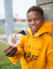 8-year-old Camron Chandler, of the Pensacola's Golden Elite Track Club, shows off his AAU medal at the Booker T. Washington High School track where he often practices in Pensacola on Thursday, September 6, 2018.