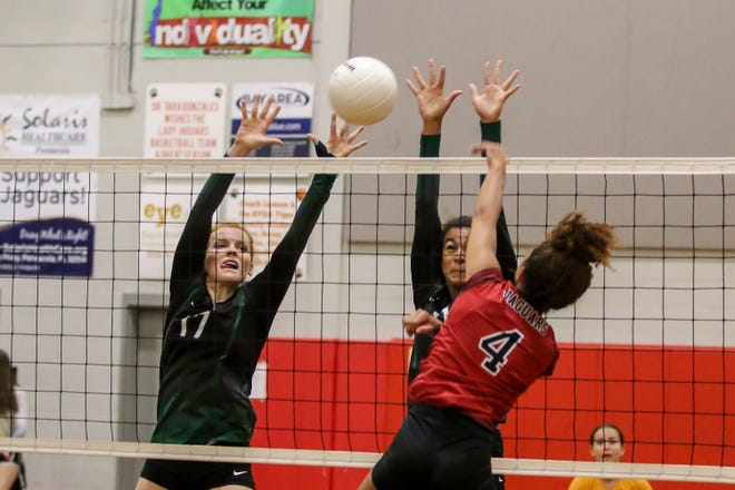 Pensacola Catholic's Hannah Meyers (17) and Amiah Butler (11) work the net and try to block a hit the Jaguars' Autumn Carter (4) at West Florida High School on Thursday, September 6, 2018.