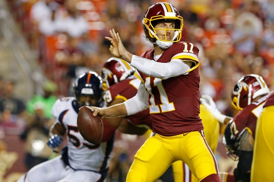 Redskins quarterback Alex Smith (11) looks to throw the ball during a game against the Broncos.