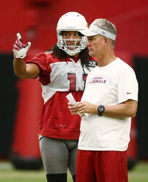 Arizona Cardinals wide receiver Larry Fitzgerald talks to offensive coordinator Mike McCoy during training camp on Aug. 15, 2018 at University of Phoenix Stadium in Glendale, Ariz.