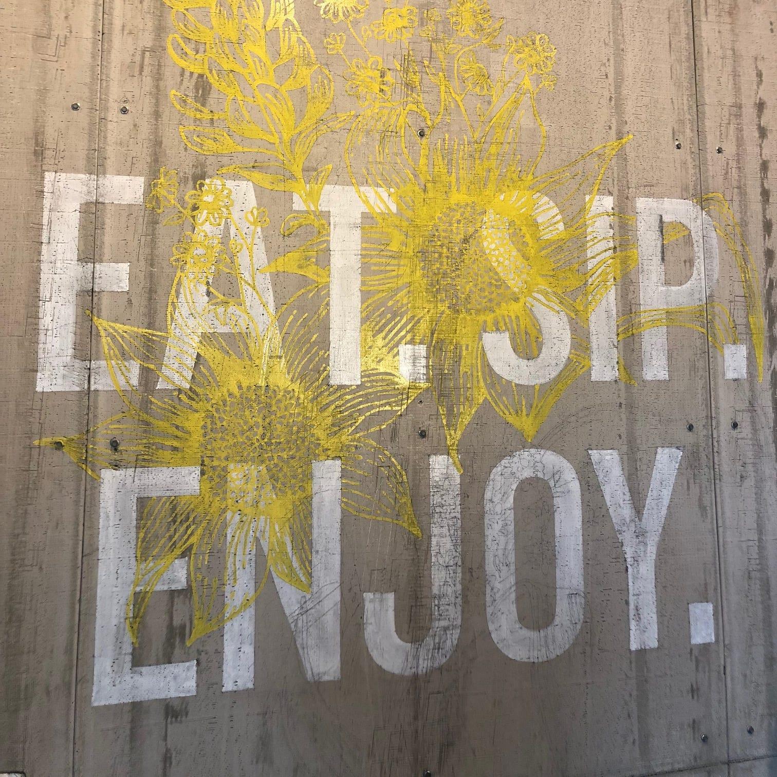 This 'Eat. Sip. Enjoy.' illustration is displayed inside Wildflower in Phoenix.