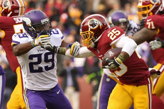 Redskins running back Chris Thompson (25) fights off a tackle from Vikings cornerback Xavier Rhodes (29).